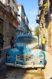 与一辆老生锈的美国汽车的街道场面在哈瓦那 库存图片