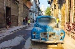 与一辆老生锈的美国汽车的街道场面在哈瓦那 免版税库存图片