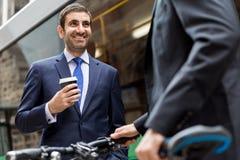 与一辆自行车的两个年轻商人在市中心 库存图片
