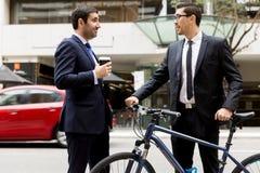 与一辆自行车的两个年轻商人在市中心 免版税图库摄影