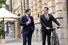 与一辆自行车的两个年轻商人在市中心 库存照片