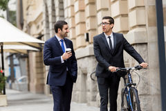 与一辆自行车的两个年轻商人在市中心 免版税库存照片