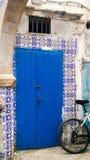与一辆自行车的传统蓝色摩洛哥门反对马赛克w 库存图片
