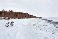 与一辆自行车的冬天风景在冻河 Ob劈裂 库存图片