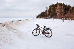 与一辆自行车的冬天风景在冻河 Ob劈裂 图库摄影