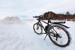 与一辆自行车的冬天风景在冻河 Ob劈裂 免版税库存照片