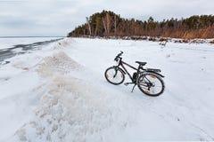 与一辆自行车的冬天风景在冻河 Ob劈裂 免版税库存图片