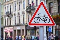 与一辆自行车的图片的一个路标反对一条拥挤街道的 允许的循环 免版税库存照片