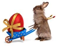 与一辆蓝色独轮车和一个红色复活节彩蛋的滑稽的复活节兔子 免版税库存照片
