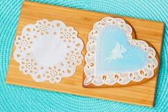 与一逗人喜爱的一点girl& x27的图象的美丽的淡色蓝色姜饼; s神仙和透雕细工小垫布,木的背景 库存图片