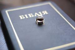 与一部圣经的两个婚戒在木桌上 免版税库存图片