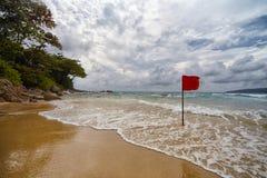 与一面红旗的偏僻的海滩 库存照片