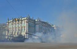 与一面红旗的坦克T-90在一阵烟幕在宫殿squa的 图库摄影
