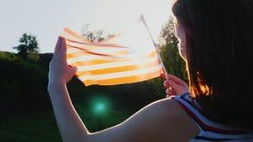 与一面美国国旗的两女性孪生在蓝天背景 回到视图 背景日减速火箭grunge的独立 影视素材