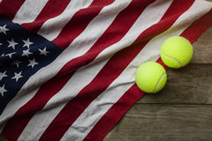 与一面美国国旗的网球在木桌上 免版税库存图片