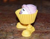 与一顶桃红色婴孩童帽的滑稽的鸡蛋在一个黄色有腿的蛋杯里面 库存图片