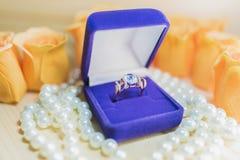 与一颗蓝色宝石的金戒指在珍珠的一个礼物盒 免版税库存照片