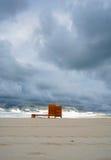 与一间木穿戴的客舱的剧烈的多云最低纲领派海滩视图 更衣室 免版税库存图片