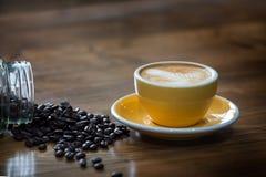 与一黄色杯的溢出的咖啡豆 免版税库存图片