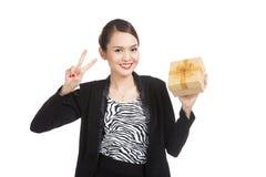 与一件金黄礼物的年轻亚洲女商人展示胜利标志 免版税库存照片