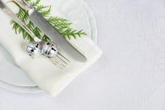 与丁当和绿色枝杈的圣诞节桌 免版税库存照片