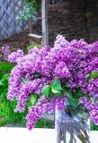 与丁香花束的美好的构成在花瓶的在白色葡萄酒鞋带桌布,灰色石墙背景 免版税图库摄影