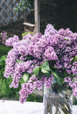与丁香花束的美好的构成在花瓶的在白色葡萄酒鞋带桌布,灰色石墙背景 库存图片