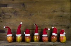 与七个红色圣诞老人帽子的滑稽的圣诞节贺卡在苹果 库存图片