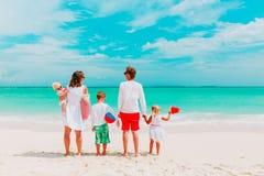 与三个孩子的愉快的家庭在海滩走 图库摄影
