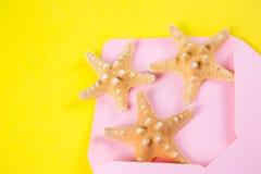 与三个海星的桃红色信封在色的黄色背景 免版税库存图片