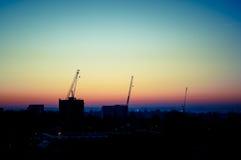与三台建筑工作起重机剪影的都市风景日出 免版税库存照片