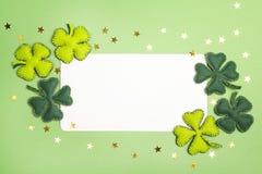 与三叶草毛毡叶子的空白的白色卡片在绿色背景的 库存照片