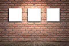 与三块帆布框架的室内部葡萄酒在图象广告的红砖墙壁,棕色木地板,三个空的框架上 免版税库存照片
