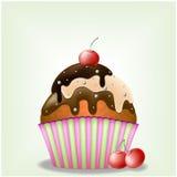与三巧克力奶油和樱桃的可口杯形蛋糕 免版税图库摄影