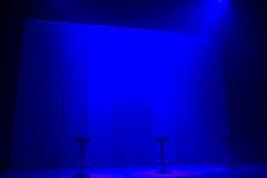 与三把凳子的蓝色阶段聚光灯 库存图片