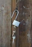 与三把房子或门钥匙的钥匙链在黑暗的木台式 免版税库存照片