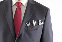 与三把扳手的商人在衣服口袋 免版税库存照片