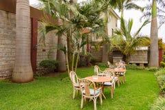 与三把铁椅子的睡觉角落在N的一个热带庭院里 免版税库存照片