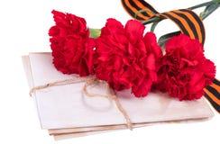 与三支红色康乃馨花束-胜利天概念的乔治丝带,隔绝在白色背景 图库摄影