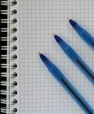 与三支蓝色笔的被摆正的螺纹笔记本笔记薄教育的,企业顶视图 免版税库存图片