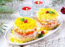 与三文鱼、土豆、乳酪、红萝卜和鸡蛋的传统俄国沙拉含羞草 库存照片