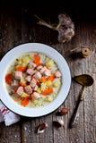 与三文鱼、土豆和红萝卜的芬兰奶油色汤在木背景的一块老葡萄酒板材 土气食物,土气样式 库存照片