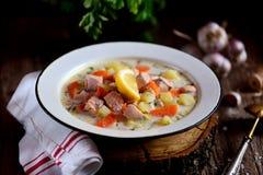 与三文鱼、土豆和红萝卜的芬兰奶油色汤在木背景的一块老葡萄酒板材 土气食物,土气样式 免版税库存图片