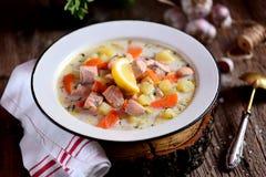 与三文鱼、土豆和红萝卜的芬兰奶油色汤在木背景的一块老葡萄酒板材 土气食物,土气样式 免版税库存照片