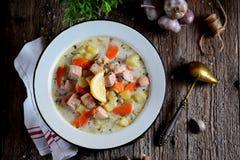 与三文鱼、土豆和红萝卜的芬兰奶油色汤在木背景的一块老葡萄酒板材 土气食物,土气样式 图库摄影