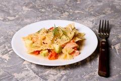 与三文鱼、夏南瓜和tomate的面团farfalle 免版税图库摄影