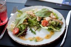 与三文鱼、草莓和樱桃的健康新鲜的沙拉 白色板材,顶视图,餐馆样式 免版税库存图片