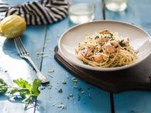 与三文鱼、荷兰芹、柠檬皮和乳酪的意大利面团 与三文鱼的新鲜的面团在一个茶碟的一个乳脂状的调味汁在木的蓝色 图库摄影