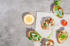 与三文鱼、蕃茄、乳酪和蓬蒿pesto的意大利bruschetta在灰色具体或石背景 免版税库存图片
