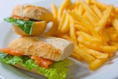 与三文鱼、蕃茄、乳酪和金黄炸薯条土豆的三明治 库存图片